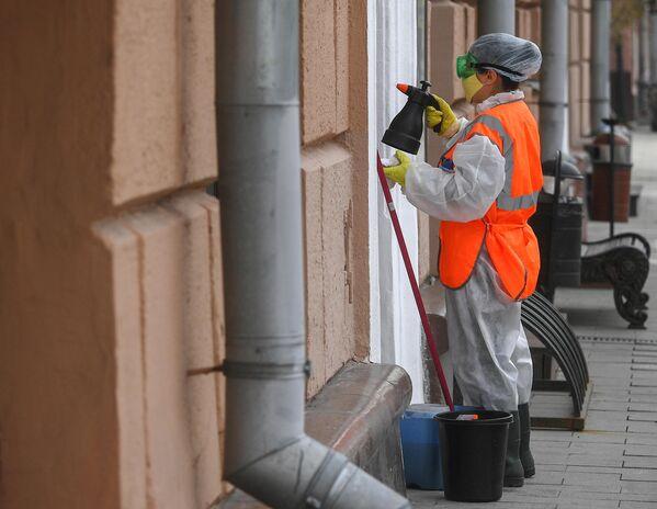 Сотрудница коммунальной службы проводит дезинфекцию в центре Москвы