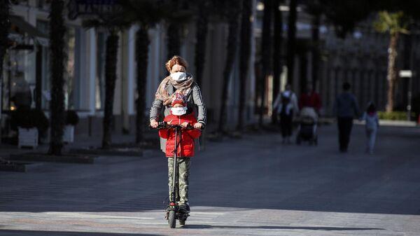 Женщина с ребенком едет на электросамокате в Ялте