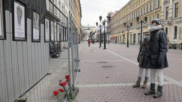 Прохожие у стены памяти умершим от коронавируса медикам в Санкт-Петербурге