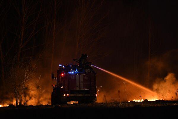 Сотрудники пожарной службы тушат полевой пожар в Новосибирской области