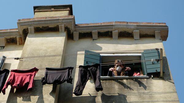Женщина выглядывает в окно в Италии