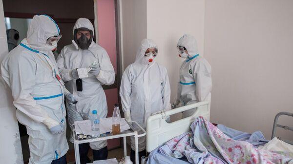 Пациент и медицинские работники в отделении реанимации и интенсивной терапии в стационаре для больных с коронавирусной инфекцией