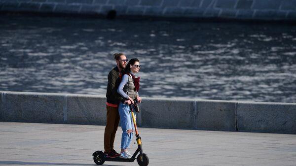 Пара едет на самокате по Москворецкой набережной в Москве