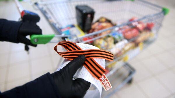 Георгиевская ленточка в руках покупателя в магазине Карусель в Москве