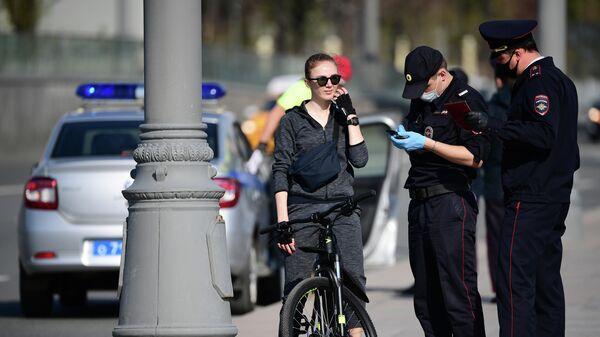 Сотрудники полиции проверяют документы у девушки на велосипеде на Москворецкой набережной в Москве.