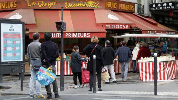Покупатели в очереди возле магазина в Париже, Франция