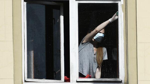 Девушка в защитной маске в квартире жилого дома в Москве