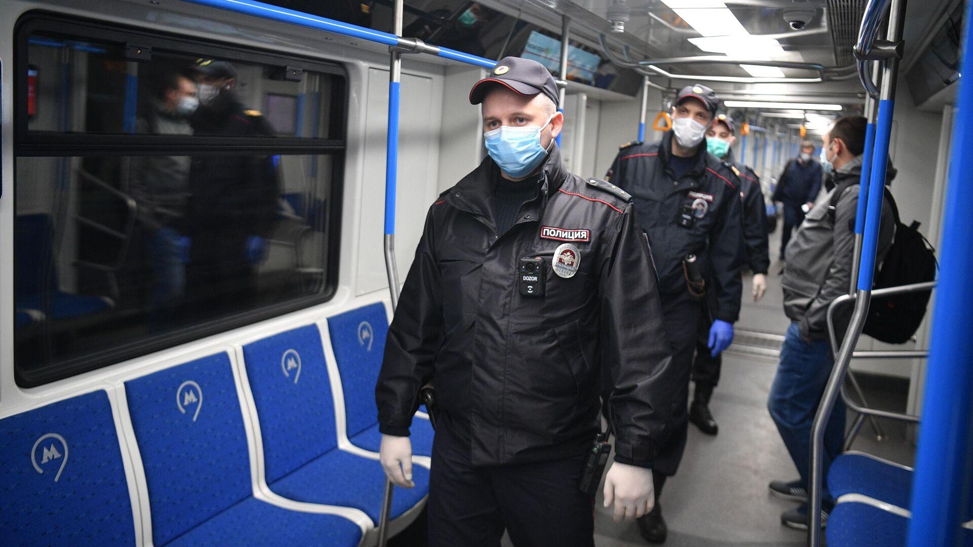Сотрудники полиции в защитных масках в вагоне московского метро  - РИА Новости, 1920, 09.06.2021