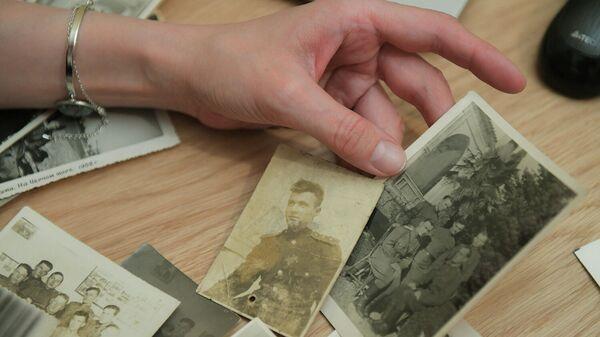 Жительница Москвы отбирает фотографии для участия в акции Бессмертный полк онлайн