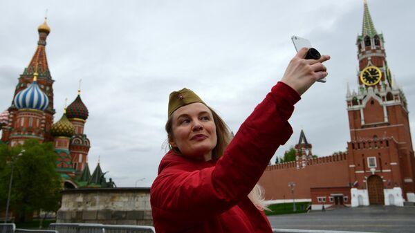 Женщина делает селфи на Красной площади в Москве во время празднования Дня Победы