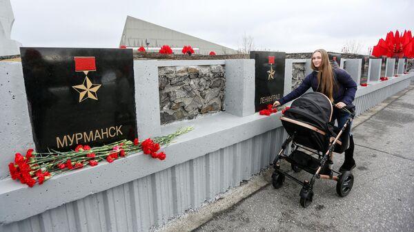 Девушка возлагает цветы к обелиску Города-герои в Мурманске