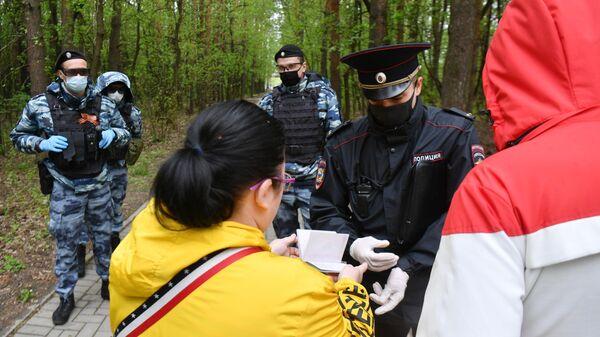 Сотрудник полиции совместно с сотрудниками Росгвардии проверяют документы у прохожих в Москве