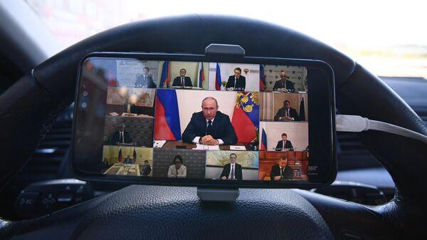 Мужчина смотрит трансляцию обращения президента России Владимира Путина в связи с ситуацией, связанной с распространением коронавируса в своем автомобиле в Москве