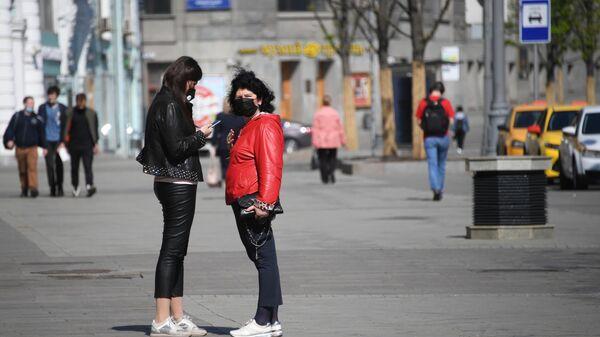 Девушки в медицинских масках на одной из улиц в Москве