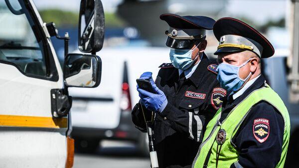 Сотрудники дорожно-патрульной службы ГИБДД во время проверки наличия пропуска у водителя на блокпосту в Москве