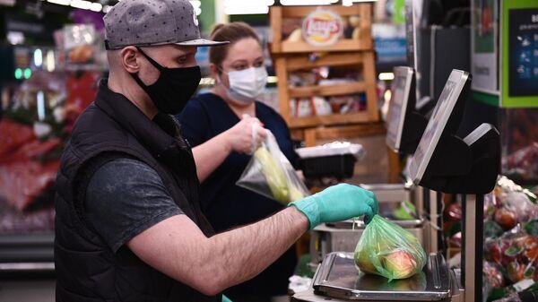 Покупатель взвешивает фрукты в продуктовом магазине в Москве