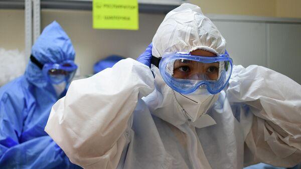 Медицинские работники надевают средства индивидуальной защиты перед входом в красную зону в городской клинической больнице имени В. В. Виноградова, переоснащенной для лечения пациентов с  COVID-19
