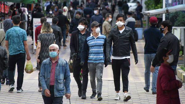 Прохожие в защитных масках на одной из улиц в Душанбе