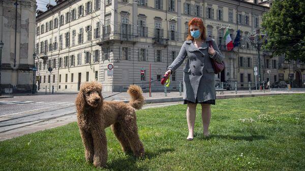 Женщина гуляет с собакой в центре города в Турине