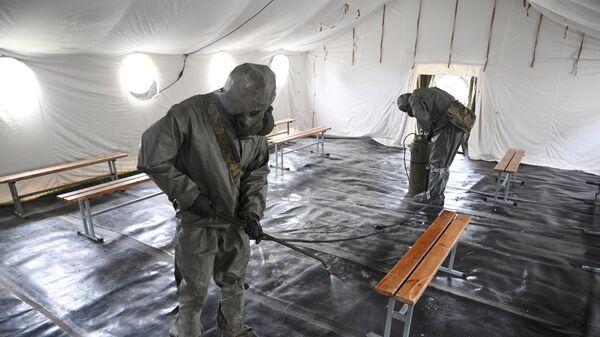Военнослужащие подразделения войск радиационной, химической и биологической защиты дезинфицируют помещение