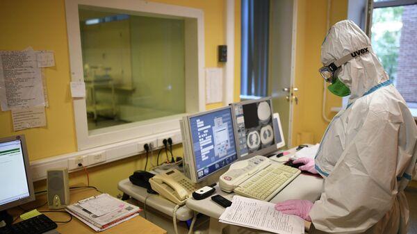 Врач смотрит показания аппарата компьютерной томографии во время обследования пациента в центральной клинической больнице РЖД-Медицина в Москве, где проходят лечение больные с COVID-19