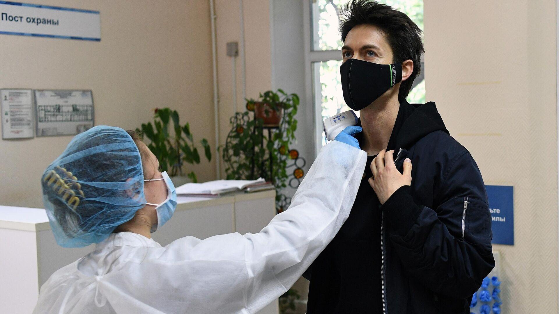 Медицинский работник измеряет температуру у мужчины перед сдачей анализа на антитела к коронавирусу COVID-19 в одной городских поликлиник в Москве - РИА Новости, 1920, 27.10.2020