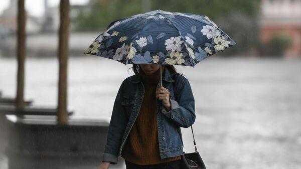 Девушка идет под зонтом во время дождя