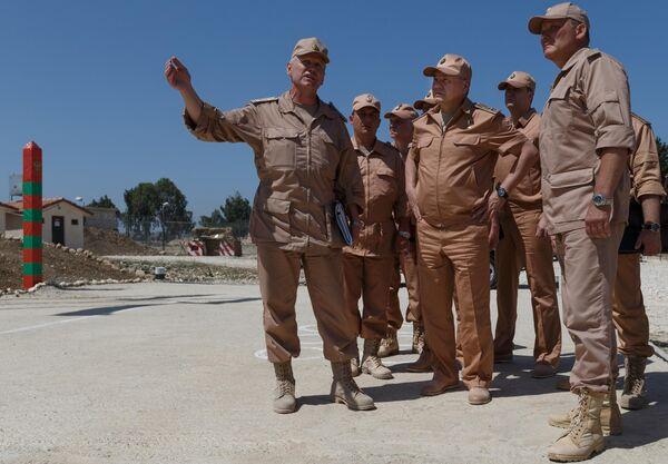 Министр обороны России Сергей Шойгу (в центре) инспектирует организацию несения российскими военнослужащими боевой службы на авиабазе Хмеймим в ходе рабочей поездки в Сирию