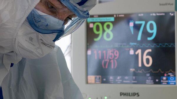 Медицинский работник возле кровати пациента в отделении реанимации и интенсивной терапии госпиталя COVID-19
