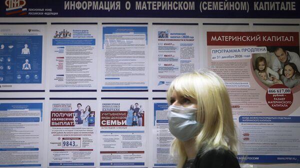Посетительница возле информационного стенда о материнском капитале в отделении пенсионного фонда