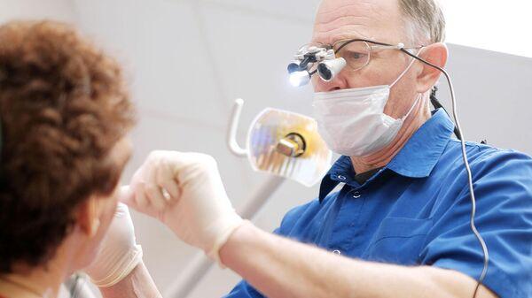 Врач-стоматолог осматривает пациента