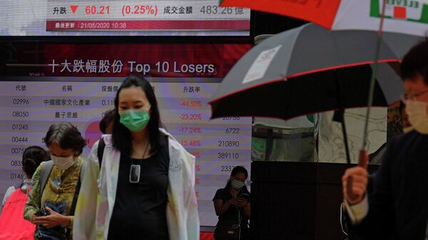 Люди проходят мимо табло с курсом индекса фондовой биржи Гонконга