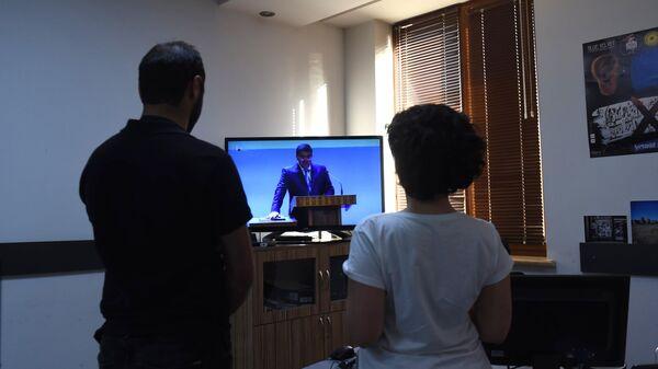 Мужчина и женщина смотрят трансляцию инаугурации избранного президента Нагорного Карабаха Араика Арутюняна