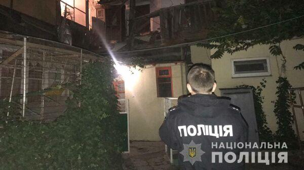Сотрудник полиции на месте обрушения фасада и крыши двухэтажного жилого дома на улице Среднефонтанская в Одессе