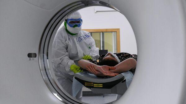Медицинский работник готовит пациентку к проведению компьютерной томографии в   госпитале COVID-19 в Центре мозга и нейротехнологий ФМБА России