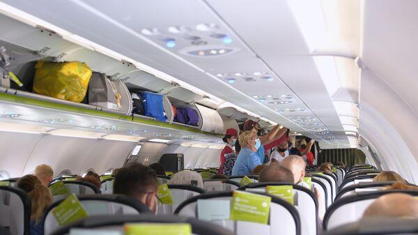 Пассажиры в защитных маска на борту самолета