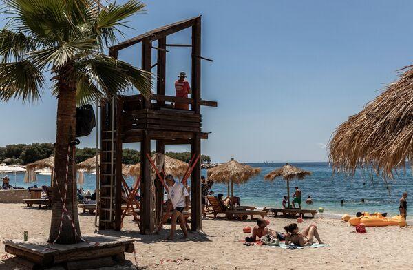 Люди на городском пляже Алимос в пригороде Афин
