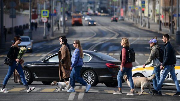 Люди переходят улицу по пешеходному переходу в Москве