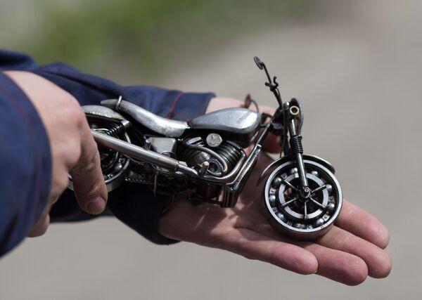 Мастер Станислав Черновасиленко держит миниатюрную копию модели мотоцикла Harley-Davidson Street 750
