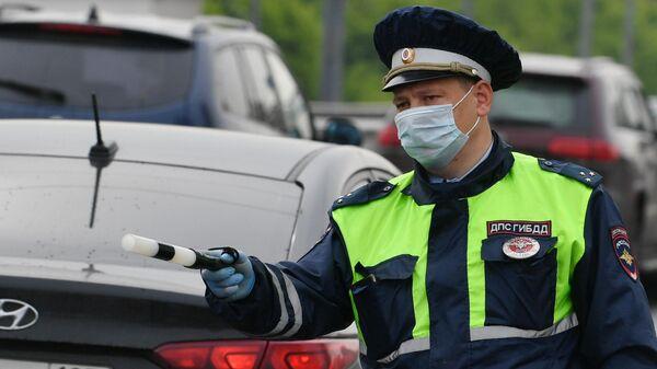 Инспектор ДПС останавливает машину для проверки цифрового пропуска у водителя