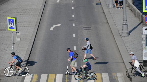 Люди пересекают дорогу по пешеходному переходу в Москве