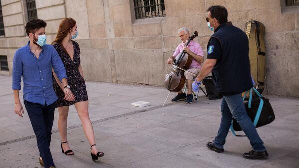 Прохожие и уличный музыкант на одной из улиц Мадрида