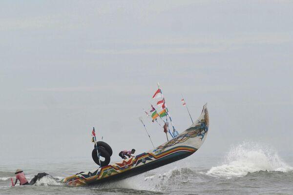 Рыбацкая лодка бьется о волны в Паданге, Суматра