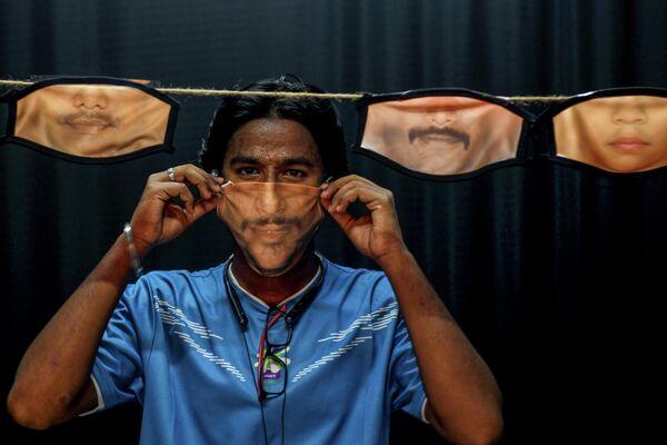Мужчина примеряет маску для лица с напечатанным на ней изображением лица