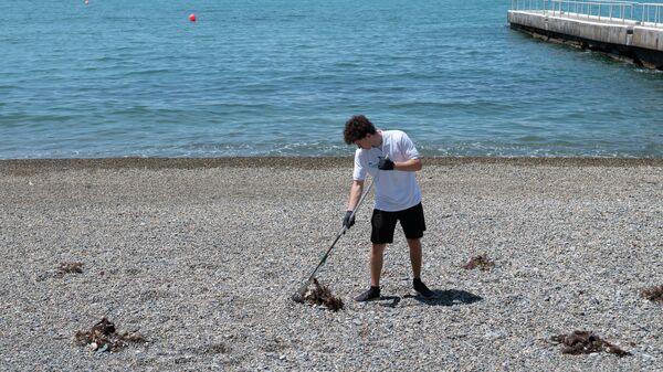 Сотрудник санатория Октябрьский в Сочи чистит пляж от мусора