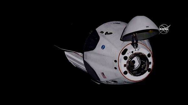 Американский корабль Crew Dragon компании SpaceX с астронавтами НАСА на борту во время стыковки с Межународной космической станцией. Стоп-кадр трансляции