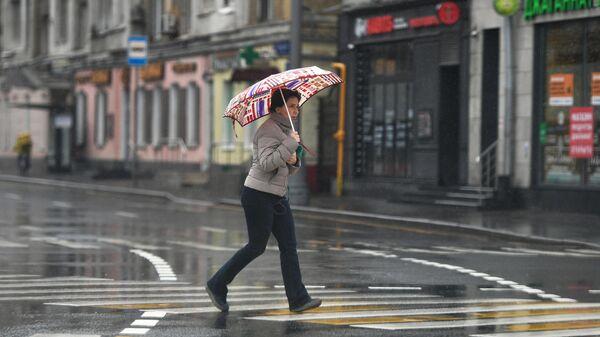 Женщина во время дождя на площади Белорусского вокзала в Москве
