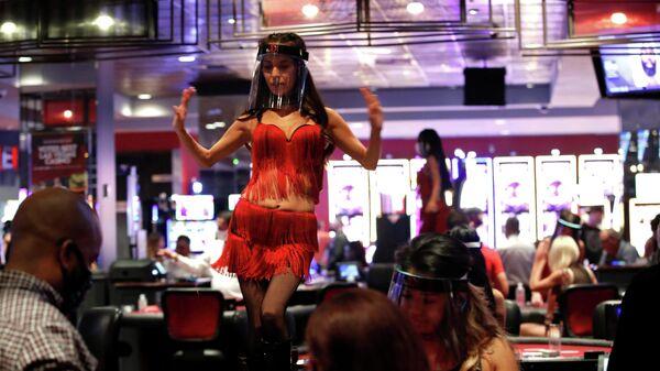 Женщина в защитной маске танцует на столе в отеле-казино Лас-Вегаса