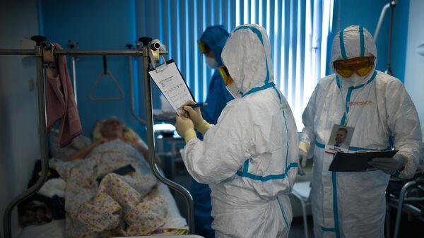 Врачи у постели пациента во время обхода в госпитале COVID-19