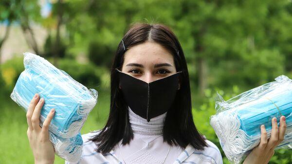 Волонтер держит в руках медицинские маски